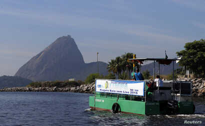 A garbage-collecting boat in seen in front of the Sugar Loaf mountain at the Guanabara Bay in Rio de Janeiro, March 12, 2014.