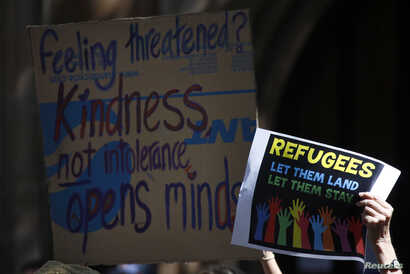 FILE - Protesters hold placards at the 'Stand up for Refugees' rally held in central Sydney, Oct. 11, 2014.