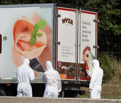 Investigators stand near a  truck that  stands on the shoulder of the highway A4 near Parndorf south of Vienna, Austria, Thursday, Aug 27, 2015.