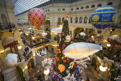 FILE - Customers walk past Christmas trees decorated for New Year celebrations in the Moscow GUM department store in Moscow, Russia, Nov. 29, 2017.