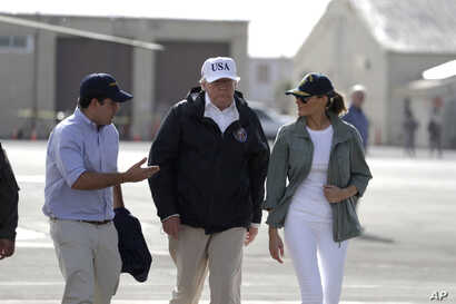 FILE - President Donald Trump and first lady Melania Trump walk with with Puerto Rico's Gov. Ricardo Rossello at the Luis Muniz Air National Guard Base before leaving the island, in San Juan, Puerto Rico, Oct. 3, 2017.