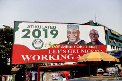 A billboard with a campaign poster bearing images of the opposition Peoples Democratic Party election candidate Atiku Abubakar and his running mate Peter Obi stands on a road in Abuja, Nigeria, Feb. 19, 2019.
