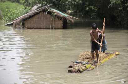 Flood affected boys move on a banana raft near partially submerged houses in Morigaon district east of Gauhati, Assam, India, Tuesday, Aug. 15, 2017.
