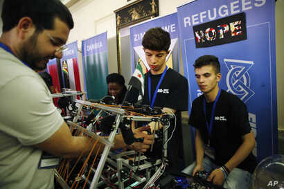 Amar Naser Kabour, center, and Mohammad Mahir Ghssan Alisawaui, right, both Syrian refugees living in Lebanon, are helped with their robot by their mentor, Osama Shadeh, who is also a Syrian refugee, during the FIRST Global Robotics Challenge, July 1...
