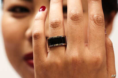 FILE - A woman shows a prototype of the Mota Smart Ring at the consumer electronic fair IFA in Berlin, Germany, Sept. 5, 2014. The smart ring is designed to notify users about incoming messages and phone calls, something, experts say, can be used to ...