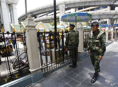 Thai soldiers walk outside the Erawan Shrine at Rajprasong intersection, the scene of last week's bombing, in Bangkok, Thailand, Aug. 24, 2015.