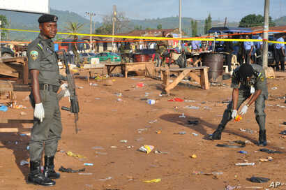 Police collect items at the site of a bomb explosion in Nyanya outskirt of Abuja, Nigeria, Oct. 3, 2015.