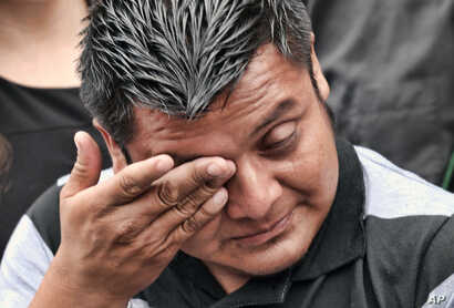 Hermelindo Che Coc, from the town of San Andres in Guatemala, wipes tears from his face during news conference prior to a required check-in with immigration enforcement authorities in downtown Los Angeles, July 10, 2018. Che Coc says his 6-year-old s...
