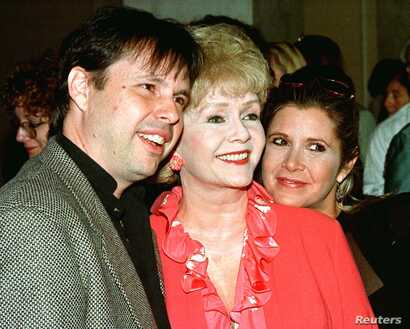 FILE - Carrie Fisher, her mother, actress Debbie Reynolds, and brother, filmmaker Todd Fisher, arrive at a luncheon hosted by the American Film Institute, Sept. 17, 1998.