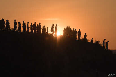 Rohingya Muslim refugees  walk down a hillside in the  Kutupalong refugee camp in Cox's Bazar on November 26, 2017.