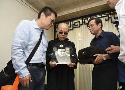 Liu Xia, wife of jailed Nobel Peace Prize winner and Chinese dissident Liu Xiaobo, holds a portrait of him during his funeral in Shenyang in northeastern China's Liaoning Province, July 15, 2017. The photo shows, from left to right, Liu Hui, younger