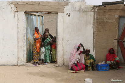 FILE - Women watch Cameroonian military patrol in Kerawa, Cameroon, March 16, 2016. Kerawa, on the border with Nigeria, was subject to frequent Boko Haram attacks.