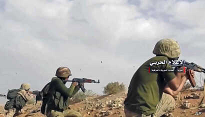 This frame grab from video provided Nov. 8, 2017, by the government-controlled Syrian Central Military Media, shows Syrian pro-government troops taking up positions and firing on militants' positions on the Iraq-Syria border.