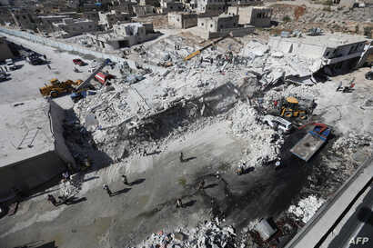 Destroyed buildings are seen, Aug. 12, 2018, following an explosion at an arms depot in a residential area in Syria's northern Idlib province city of Sarmada.