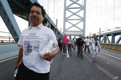 Alvaro Bautista, of Camden, N.J., walks with members of the St. Anthony of Padua Church over the Benjamin Franklin Bridge ahead of a Sunday Mass delivered by Pope Francis in Philadelphia, Sept. 27, 2015.