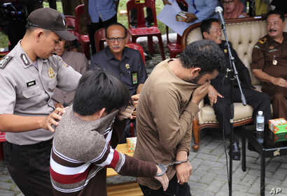 FILE - A police officer escort two men convicted of gay sex to be publicly caned at a mosque in Banda Aceh, Aceh province Indonesia, May 23, 2017.