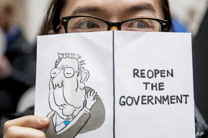 """A furloughed government worker affected by the shutdown holds a sign that reads """"Reopen the Government"""" during a silent protest against the ongoing partial government shutdown on Capitol Hill in Washington, Jan. 23, 2019."""