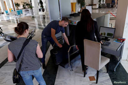 Russian tourists get their luggage back from a scanner after security check at the Steigenberger Kantaoui Bay resort, in Sousse, Tunisia, Sept. 29, 2017.
