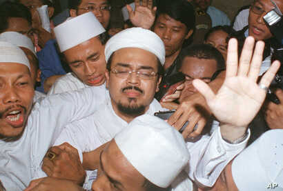 Radical Muslim cleric Habib Rizieq (center) tries to calm his supporters as they escort him away from the higher prosecutors' office in Jakarta, April 21, 2003.