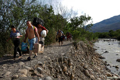 FILE - Venezuelans carry their belongings along a pathway after illegally entering Colombia through the Tachira river close to the Simon Bolivar International bridge in Villa del Rosario, Colombia, Aug. 25, 2018.