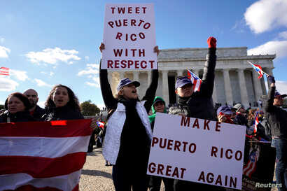 Protesters hold up signs to highlight the ongoing humanitarian and natural disaster crisis in Puerto Rico, at the Lincoln Memorial in Washington, Nov. 19, 2017.