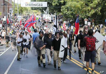 White nationalist demonstrators walk through town after their rally was declared illegal near Lee Park in Charlottesville, Va., Aug. 12, 2017.