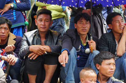 Men watch horse racing held during the Torch Festival celebrated by ethnic Yi minorities in Butuo County, Sichuan province, China, July 22, 2017.