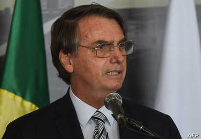 Brazil's President Jair Bolsonaro delivers a speech during the inauguration of the new Director of the Brazilian side of Itaipu binational hydroelectric dam, former Brazilian Defense Minister and Army General Joaquim Silva e Luna, Feb. 26, 2019 in It...