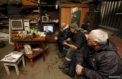 Workers watch a television broadcast of Russian President Vladimir Putin address to the Federal Assembly at an auto repair shop in the Siberian town of Divnogorsk near Krasnoyarsk, Russia, Dec. 3, 2015.