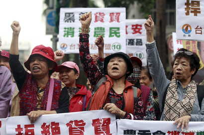 """FILE - Activists shout during a protest against trade agreement with China in front of the Council of Agriculture in Taipei, Taiwan, January 4, 2016. The placards read, """"Refuse trade agreement."""" """"Trade agreement kill farmers."""""""