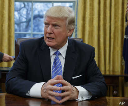 President Donald Trump sits at his desk in the Oval Office of the White House in Washington.