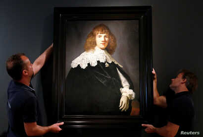 """Gallery assistants hold a Rembrandt painting called """"Portrait of a Young Man"""" at Hermitage Amsterdam in the Netherlands capital, May 16, 2018."""