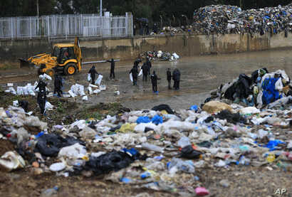 Activists from the You Stink anti-government movement remove trash from the Beirut River as it flows towards the Mediterranean Sea, in Karantina, east Beirut, Lebanon, Oct. 25, 2015.