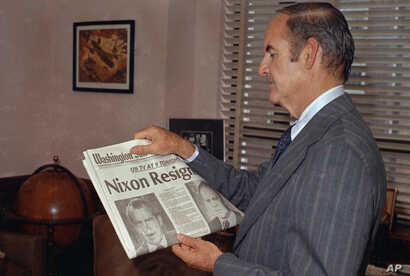 Sen. George McGovern (D-SD) reads the newspaper headline of Pres. Nixon?s resignation, Aug. 7, 1974.