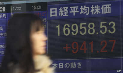A woman walks past an electronic stock board showing Japan's Nikkei 225 that gained 941.27 points or 5.88 percent and closed at 16,958.53 at a securities firm in Tokyo, Jan. 22, 2016.