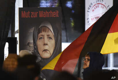 """FILE -A poster with the writing """"Courage to speak the truth"""" depicts German Chancellor Angela Merkel wearing a veil  during a demonstration of the Legida anti-Islamization movement, an offshoot of Pegida, in Leipzig, Jan. 30, 2015."""