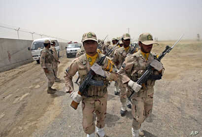 FILE - A group of Iranian border guards march at the eastern border of Iran shared with Pakistan and Afghanistan, near Zabol, Sistan-Baluchistan Province, Iran, July 19, 2011.