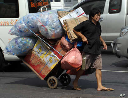FILE - A man pulls a trolley filled with used plastic bottles on a street in Bangkok, Thailand.