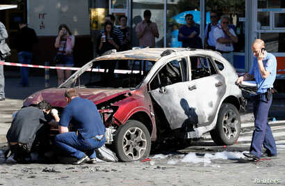 Investigators inspect a damaged car at the site where journalist Pavel Sheremet was killed by a car bomb in central Kiev, Ukraine, July 20, 2016.