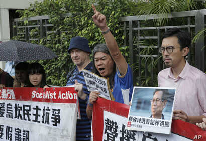Protesters holding signs and a picture of Wukan village chief Lin Zulian are seen at a solidarity rally outside the Chinese central government's liaison office in Hong Kong, Sept. 9, 2016.