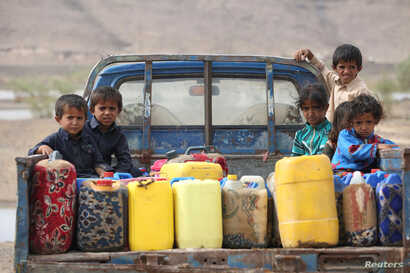 Children ride on the back of a truck loaded with water jerrycans at a camp for internally displaced people in the Dhanah area of the central province of Marib, Yemen, April 30, 2016.