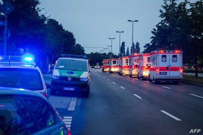 Police cars and ambulances are seen near a shopping mall (the Olympia Einkaufzentrum (OEZ) ) in Munich on July 22, 2016 following shootings.