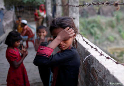 FILE - A Rohingya refugee girl wipes her eyes as she cries at Leda Unregistered Refugee Camp in Teknaf, Bangladesh, Feb. 15, 2017.