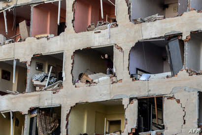 A woman reacts in her damaged apartment on the explosion site, Nov. 4, 2016 after a strong blast in the southeastern Turkish city of Diyarbakir.