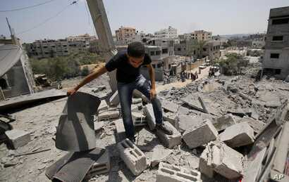 A member of the Abed Aal family salvages belongings from his family's house destroyed in an overnight Israeli strike in Gaza City, Aug. 2, 2014.