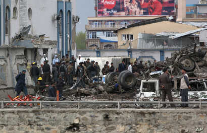 Afghan security forces inspect the site of a Taliban-claimed deadly suicide attack in Kabul, Afghanistan, April 19, 2016.