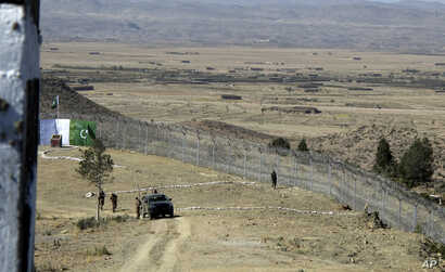 Pakistani soldiers stand guard at a newly erected fence between Pakistan and Afghanistan at Angore Adda, Pakistan, Oct. 18, 2017.