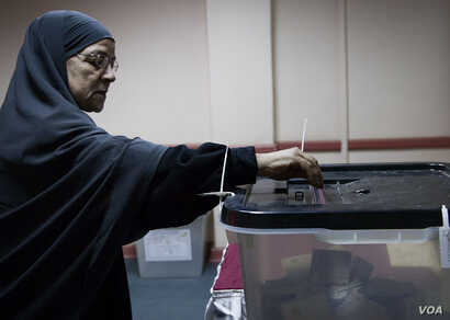 An Egyptian woman casts her ballot in Giza, Saturday, Dec. 22, 2012. (Yuli Weeks for VOA).