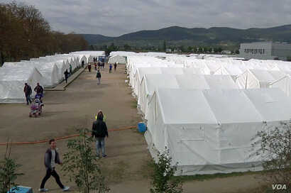 Migrants and asylum-seekers are seen walking on the grounds of the make-shift reception center in Traiskirchen, Austria. (Photo - VOA video grab)