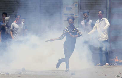 A Kashmiri Muslim protester throws back a teargas shell at Indian paramilitary soldiers in Srinagar, Indian-controlled Kashmir, July 10, 2016.